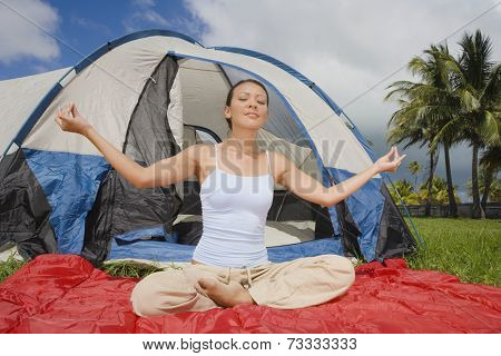 Hispanic woman meditating in front of tent