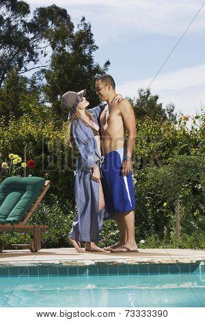 Multi-ethnic couple hugging next to swimming pool