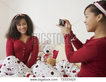 African twin sisters taking photograph