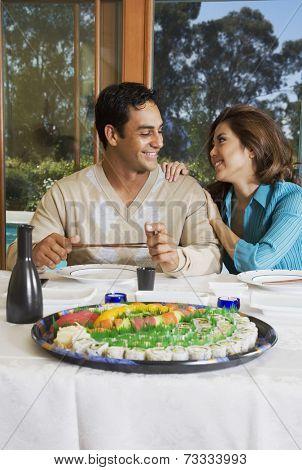 Multi-ethnic couple eating sushi