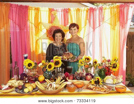 Mixed Race mother and daughter behind buffet table