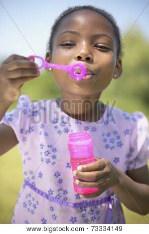 African girl blowing bubbles
