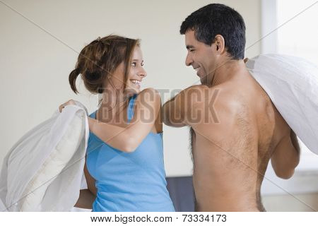 Hispanic couple having pillow fight