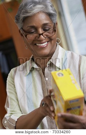 African woman reading food ingredients