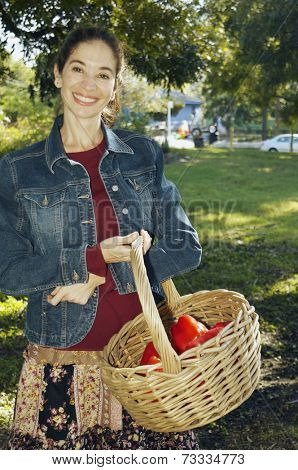 Middle Eastern woman carrying basket of organic produce