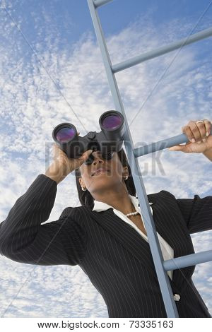 African businesswoman looking through binoculars on ladder