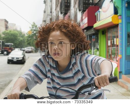Mixed Race boy riding bicycle