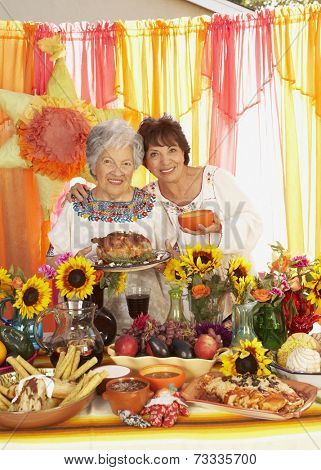 Hispanic woman and adult daughter behind buffet table