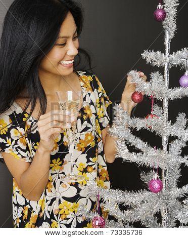 Pacific Islander woman decorating Christmas tree