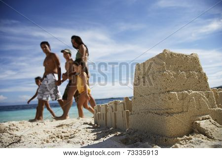 Hispanic family walking past sandcastle