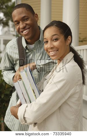 African couple carrying books and backpack