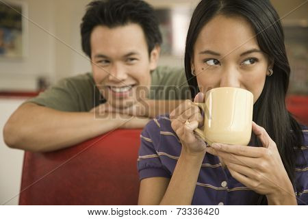 Asian man watching woman drink coffee