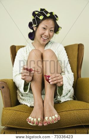 Asian woman painting toenails