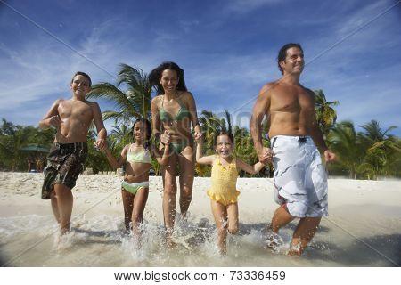 Hispanic family running into water