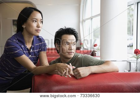 Asian couple leaning on diner booth
