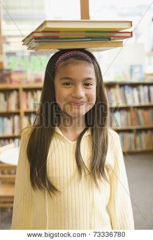 Pacific Islander girl balancing library books on head