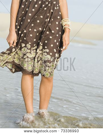 African woman wading in ocean surf