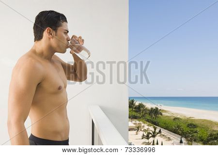 Bare-chested Hispanic man drinking water