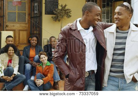 African men hugging with friends in background