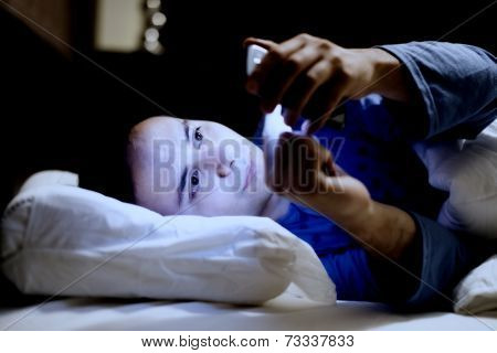 Man using his mobile phone in the bed