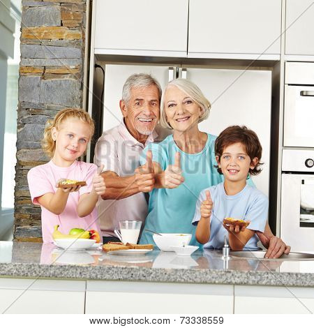 Grandparents and grandchildren holding thumbs up during breakfast in kitchen