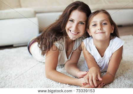 Mother with her preteen daughter having fun on a white carpet in living room at home
