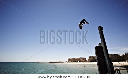 boy doing a backflip from a pier