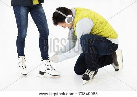 A picture of a young man tying his friend's skates on a skating rink