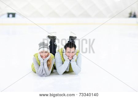 A picture of a happy couple lying on the skating rink