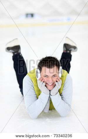 A picture of a happy man lying on the ice rink