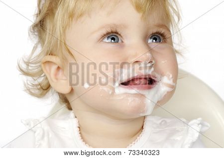 The baby girl eating and smiling with white background