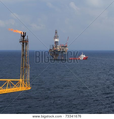 Jack up drilling rig flare boom and crew boat in the middle of the sea
