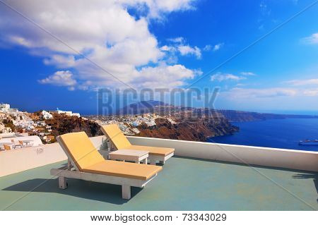 Two deckchairs on the roof of the building on Santorini island, Greece. View on Caldera and Aegean sea, sunny day, blue sky.