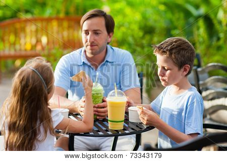Young father and his two kids at outdoor cafe on summer day