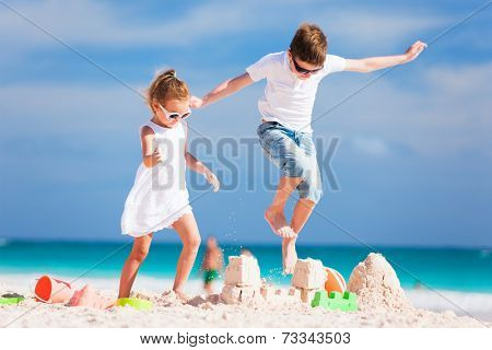 Two kids having fun on summer vacation crushing sandcastle