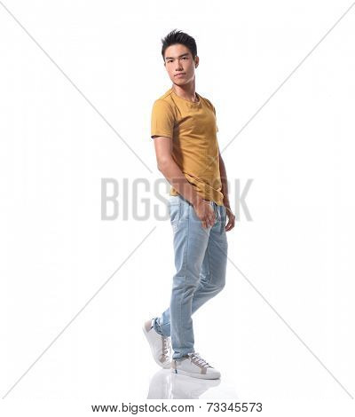 portrait of a side view young casual man walking in studio