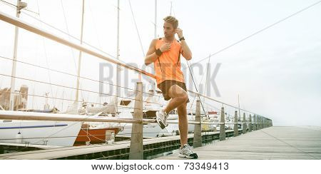 Young attractive runner enjoying a morning run along the promenade