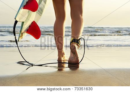 Young beautiful surfer girl on beach with surf board