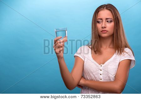 Portrait of young beautiful girl holding a glass with clean wate