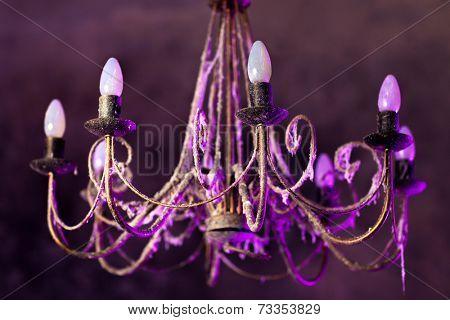 Retro chandelier with soft purple light.