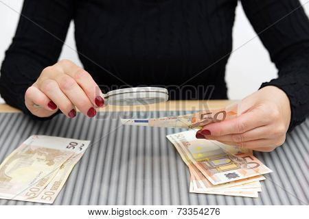 Woman Is Looking Through A Magnifying Glass For Counterfeit Money