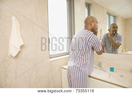 Hispanic man shaving face