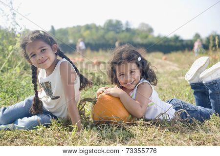 Hispanic sister sitting next to pumpkin