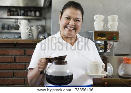 Hispanic waitress holding coffee pot and mug