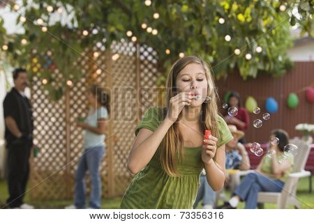 Hispanic girl blowing bubbles