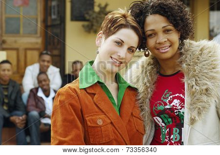 Multi-ethnic women hugging with friends in background