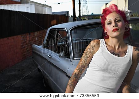 Tattooed Hispanic woman leaning on car