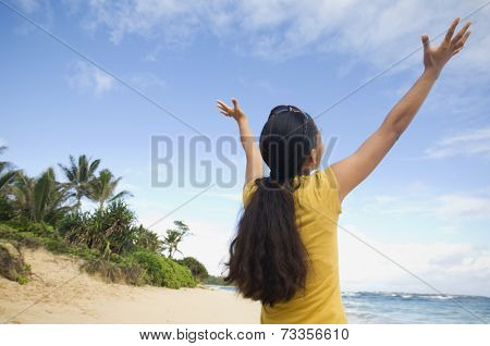 Pacific Islander woman with arms raised at beach