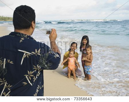 Pacific Islander father taking photograph of family