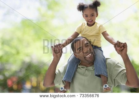Mixed Race girl sitting on father's shoulders
